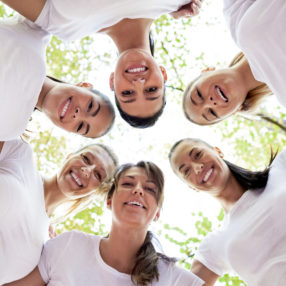 Group of women standing in the circle, smiling at the camera, low angle view.